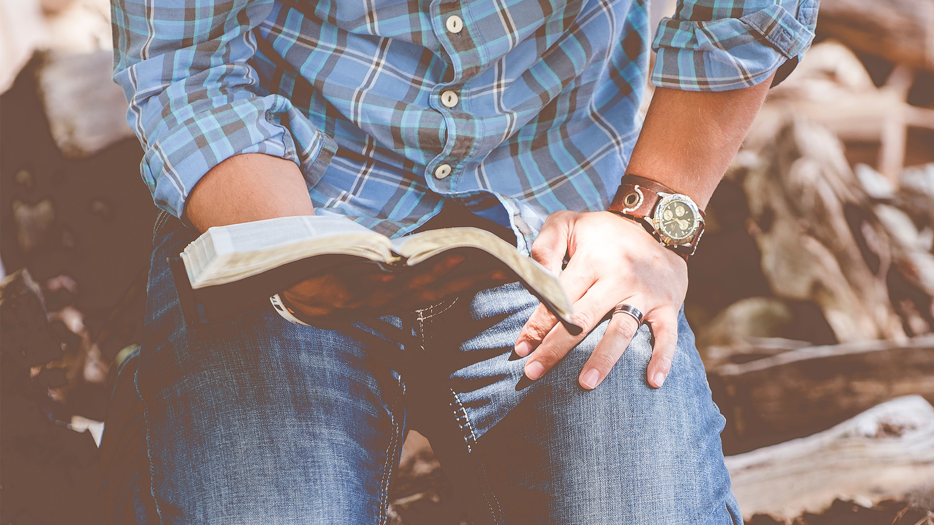 person-reading-book-while-kneeling