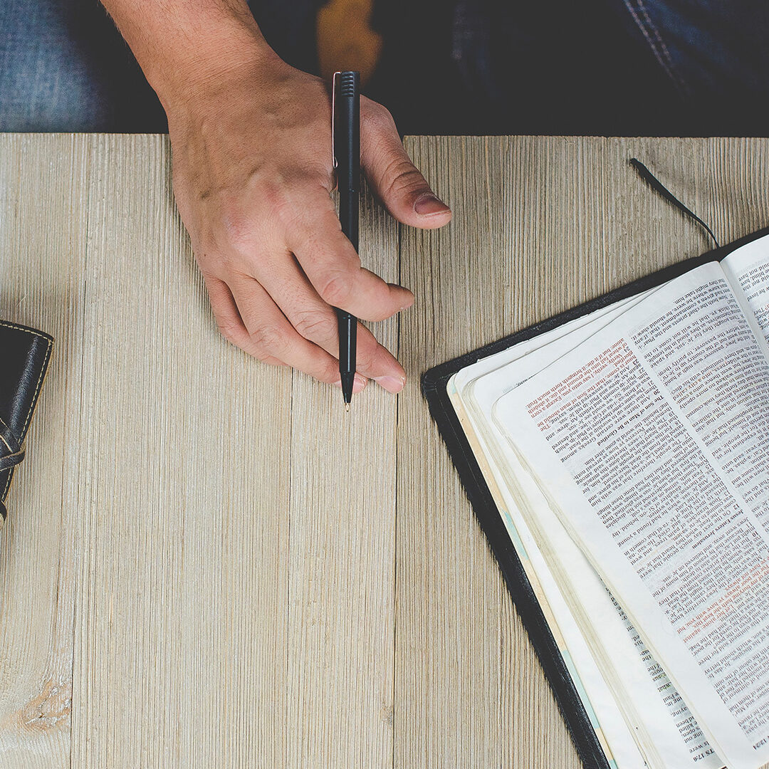 person-holding-bible-with-pen